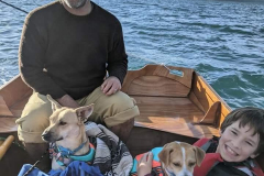 Curtis-Havel-and-son-Declan-sailing-their-home-built-Passagemaker-Dinghy-22Rising-Phoenix22-across-Tomales-Bay-with-our-salty-dogs-Calixo-and-Rocky