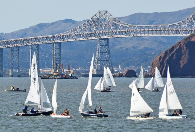 Small boats racing in front of the Richmond-San Rafael Bridge