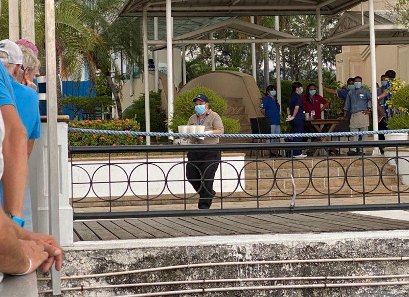 Masked man bringing drinks