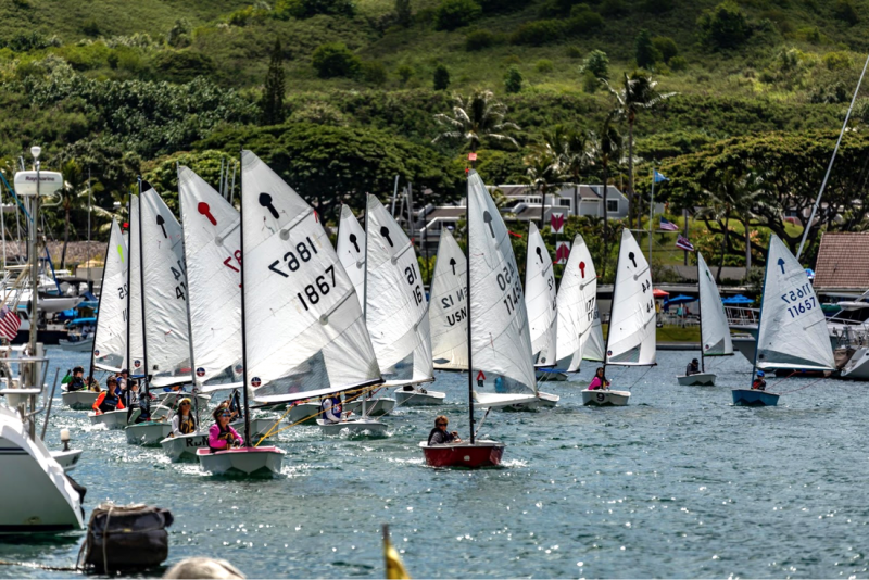 A large number of 8 foot El Toro sailboats with Junior sailors leaves the harbor at Kaneohe Yacht Club.