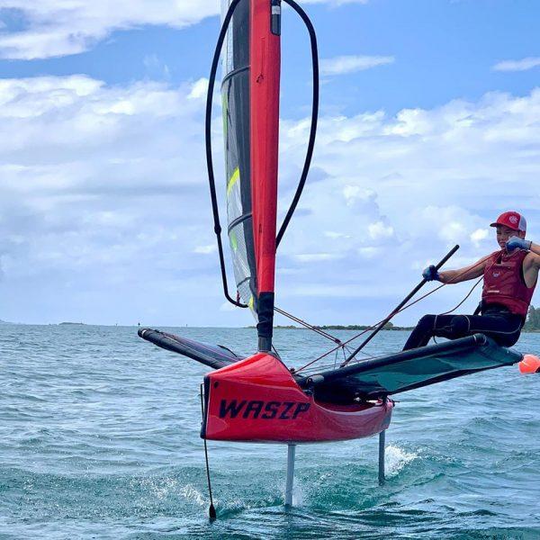 A sailor rides a foiling Waszp on hydrofoils.