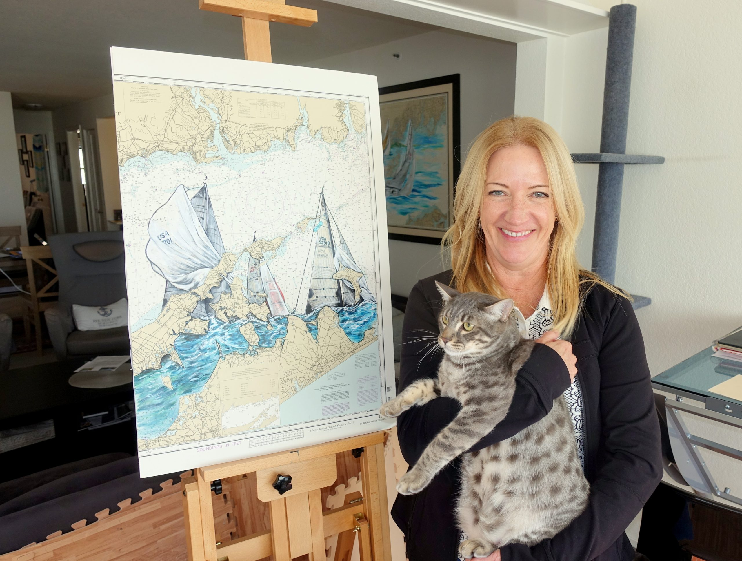 Denise Kramer stands by her painting, holding her cat.