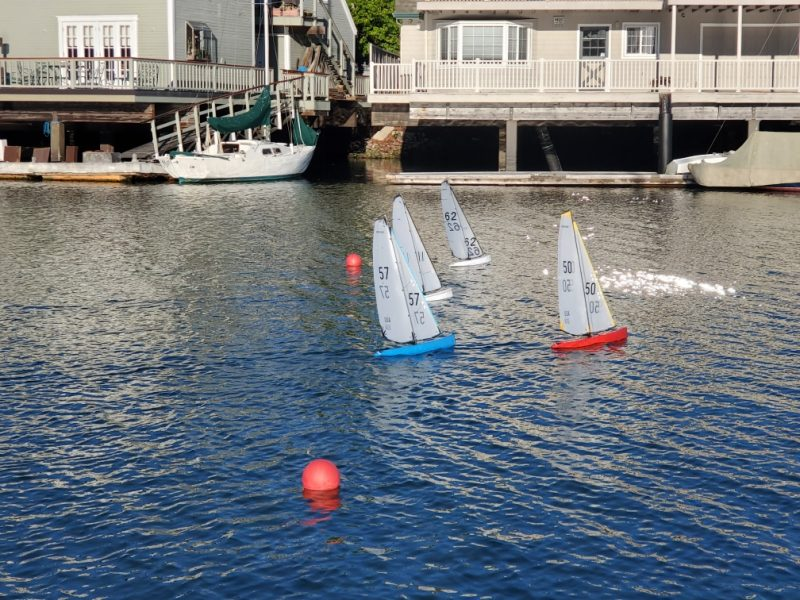 Four model sailboats start a race at Richmond Yacht Club