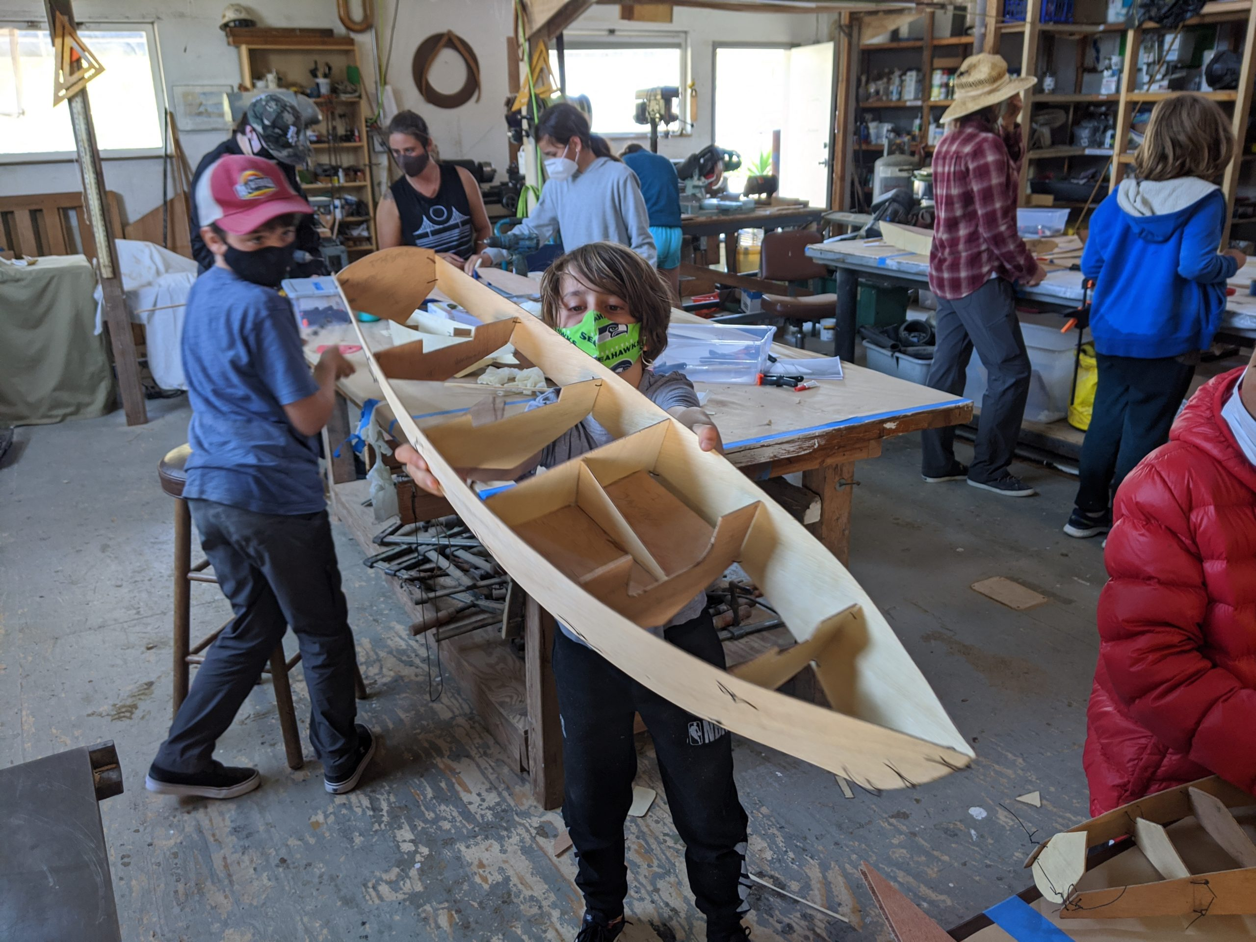 Masked youth holding model boat