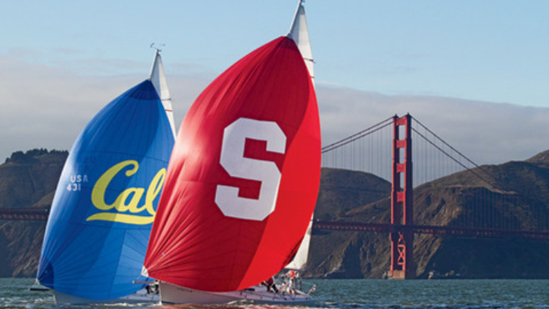Two J105 sailboats with spinnakers showing Stanford and Cal logos