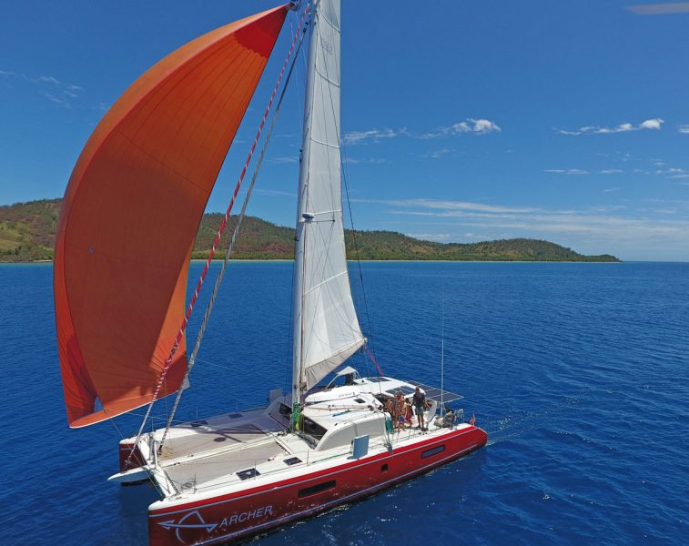 red catamaran with orange spinnaker