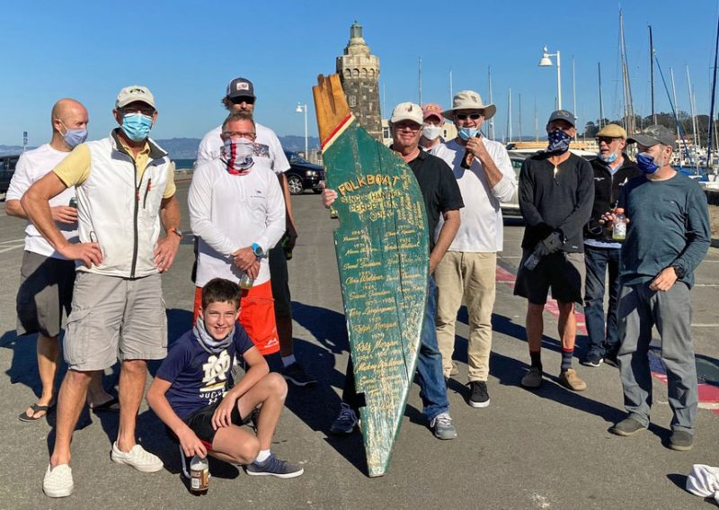 Sailors in parking lot with Folkboat rudder