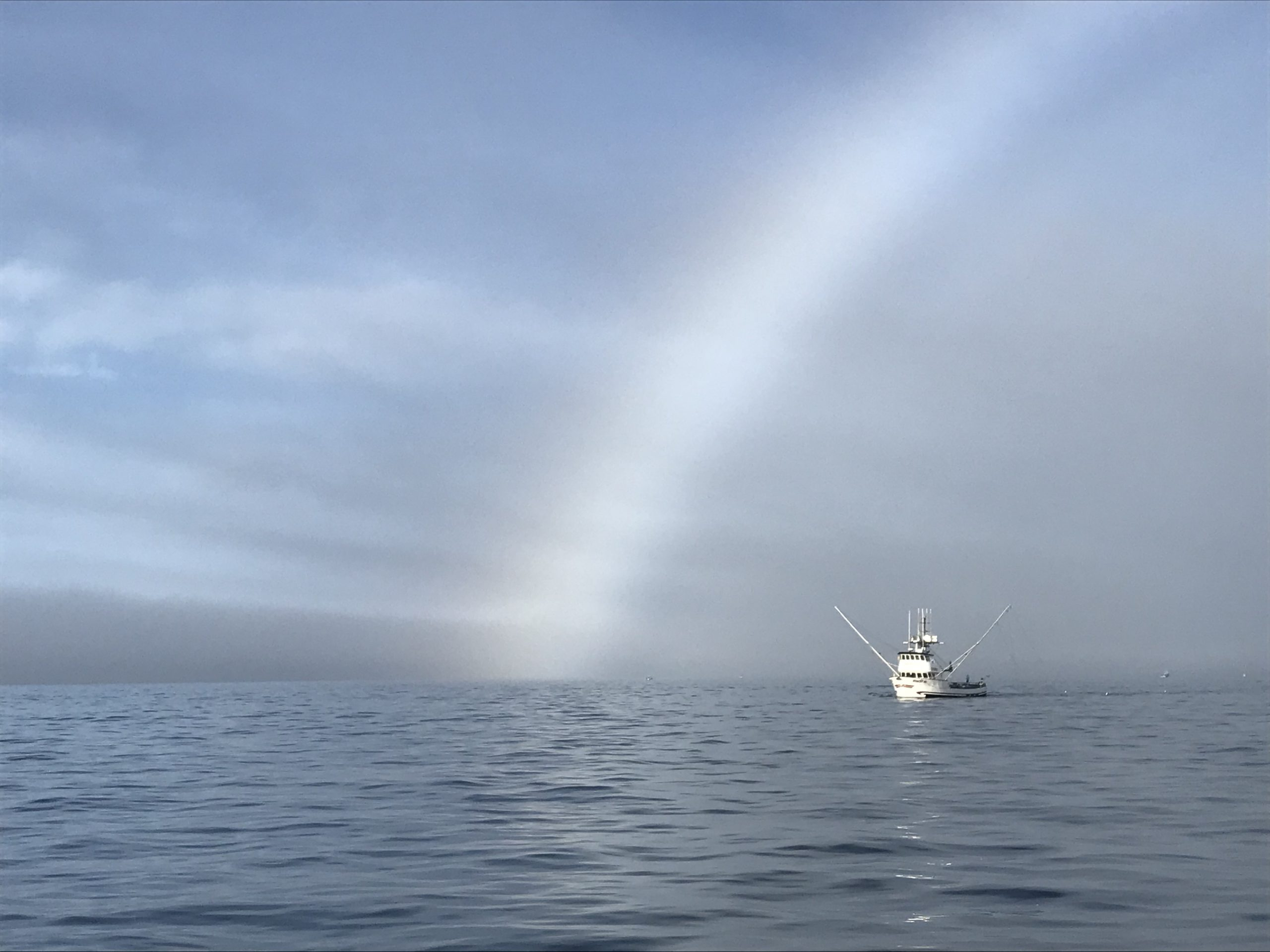 Fishing boat under fogbow
