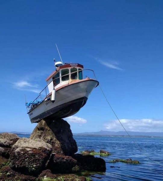 Anchored Boat High and dry on Rock