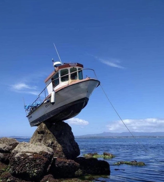Caption Contest (!) Anchored Boat High and dry on Rock