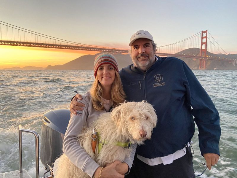 Tina, Cooper and Chris on a boat with the sun setting behind the Golden Gate Bridge