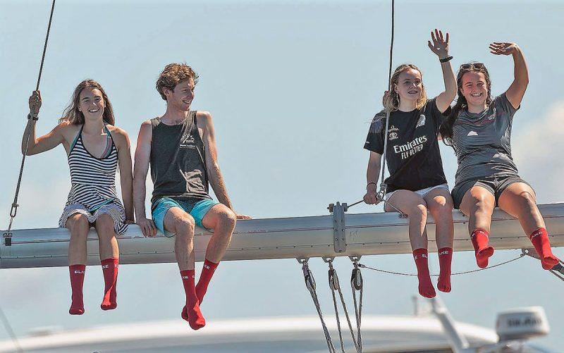 Fans wearing red socks, sitting on a boom